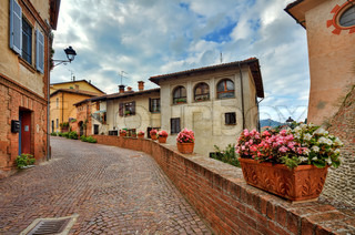Narrow cobbled street among medieval colorful houses at town of Barolo in Piedmont, Northern Italy