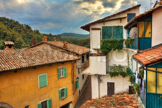 Fragment of small italian town with colorful houses, roofs covered by tiles and small balconies under the autumnal cloudy sky in Barolo, Italy