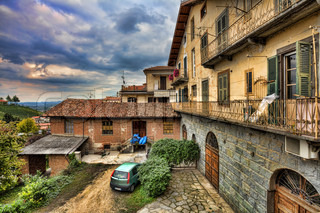 View on traditional italian courtyard among old houses under cloudy autumnal sky in town of Barolo, Italy