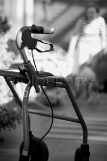 greyscale closeup of rollator standing in front of blurred senior woman,