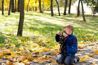Small boy using a vintage slr camera