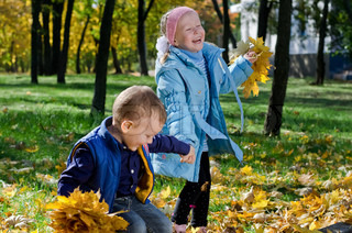 Laughing children playing with fall leaves
