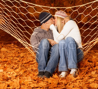 Loving pair kissing in hammock