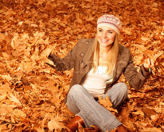 Girl throwing up autumnal leaves