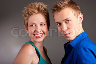 Cheerful young couple standing in studio