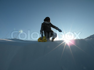 Girl standing in deep snow, pointing at the low sun
