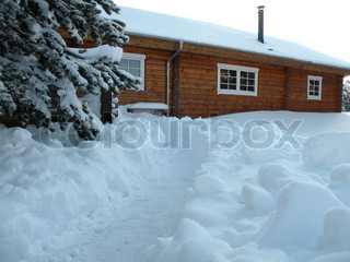 block house in winter surrounded with much deep snow