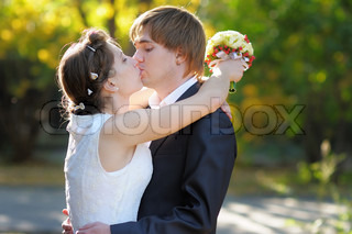 Beautiful bride and groom kissing outdoors