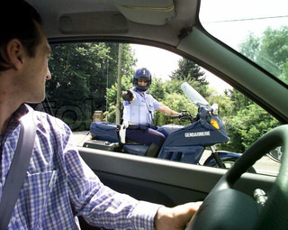Side view from inside of a car, policeman pointing out towards the driver