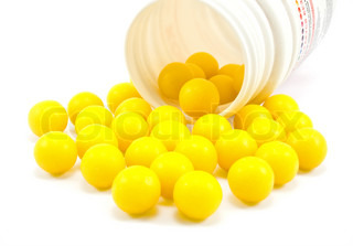 Yellow pills from bottle on the white