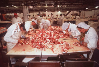 Worker cutting meat on table at slaughterhouse