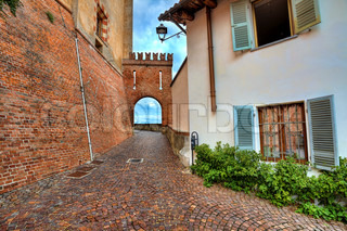 Narrow cobbled street among house and brick wall of medieval castle in Barolo, Italy