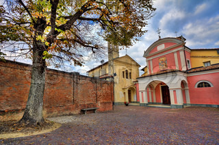 Big tree on small cobbled courtyard among brick wall and church with colorful red walls in town of Barolo, Italy.