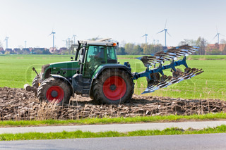 Tractor with plowes on the spring field