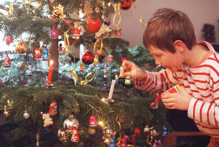A boy lighting candle on a Christmas tree