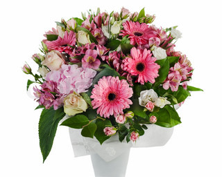 colorful floral bouquet of roses, lilies and orchids arrangement centerpiece in vase isolated on white background