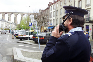 Police officer using walkie-talkie on street