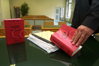 Close-up view of a human hand opening a law book