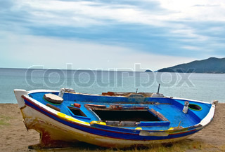 fishing boat on sand with cloudy blue sky and water