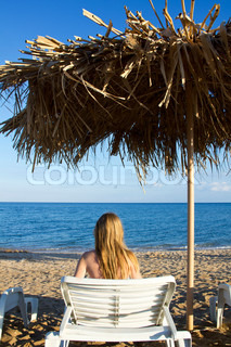 Young woman lying in the deck-chair in front of the sea