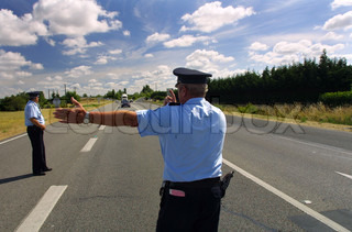 Rear view of traffic police directing the traffic on the road
