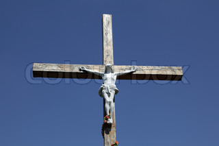 Stone statue of Jesus Christ crucified on a wooden cross