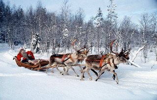 Santa riding on his sleigh with 4 reindeer