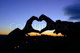 Silhouette of hands in form of heart when sweethearts have touched in autumn