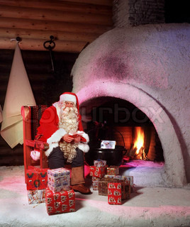 Santa Claus next to a fireplace with Christmas presents