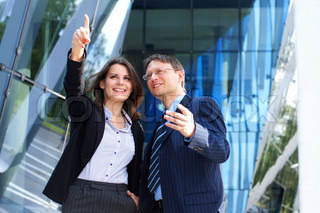 Conceptual photo of businessman showing something to his female assistant