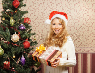 Beautiful teenager girl with the present near the Christmas tree