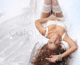 Young and sexy redhead woman in white lingerie over snowy background