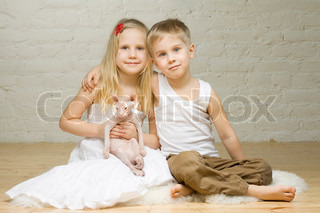 Young smiling couple - little girl and boy - with kitten sphynx