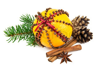 Christmas clove and orange pomander with spices, pine cones and spruce branch on white