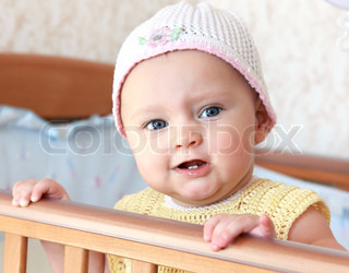Beautiful angry baby girl in funny hat standing in bed and looking