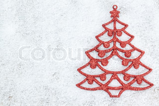 Decorative red Christmas tree on white snow