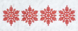 Four decorative Christmas snowflakes closeup on snow