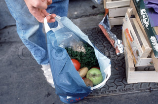 Close-up of a human hand holding bag of unsold fruits picked up from he street