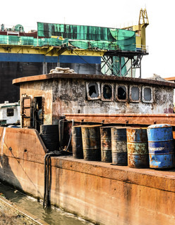 The abandoned old rusty ship in the shipyard