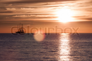 Sea sunset on fire with sail ship silhouette