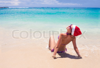 young woman in santa hat sitting on tropical beach christmas an