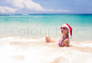 young woman in santa hat having fun in the tropical sea, christm