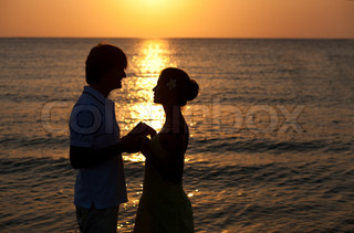 sunset silhouette of happy young lovers on the beach honeymoon