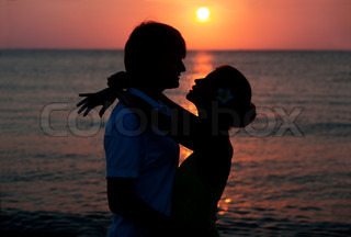 romantic young couple sunset silhouette on beach honeymoon