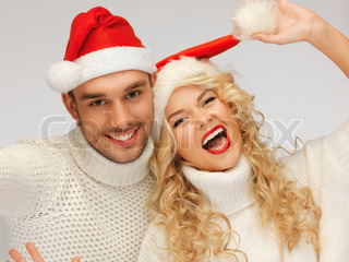 family couple in sweaters and santa's hats