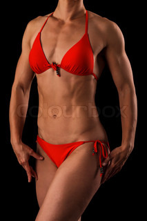 Muscular female body against black background.