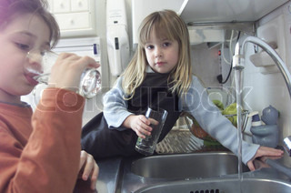 Portrait of a girl sitting on sink with open tap and sister drinking water