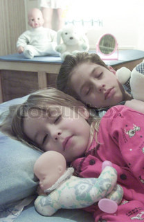 Boy and girl sleeping in bed at home with toys around