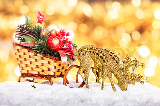 Christmas sleigh with decor and reindeers in the snow