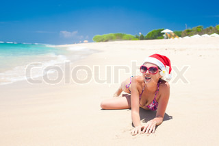 young woman in santa hat laughing at beach, christmas, new year